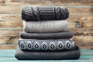 pile-of-knitted-winter-clothes-on-wooden-background-sweaters-knitwear-62130832